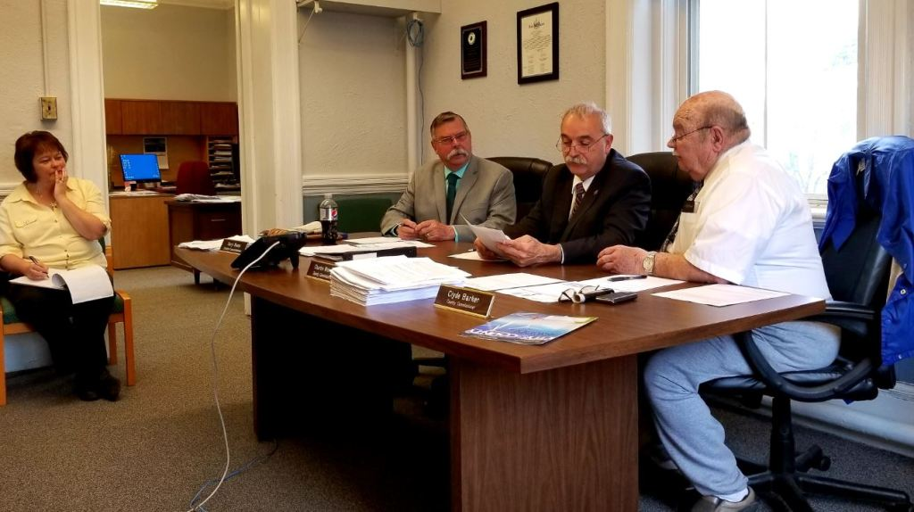 From left, county Finance Manager Vickie Braley looks on as Franklin County Commission Chairman Terry Brann, of Wilton; Charles Webster, of Farmington; and Clyde Barker, of Strong, discuss business at the Franklin County Courthouse in Farmington.