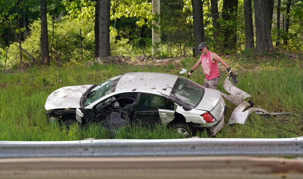 A man picks up debris around a car that went off the southbound lane of the Maine Turnpike in Scarborough on Tuesday.