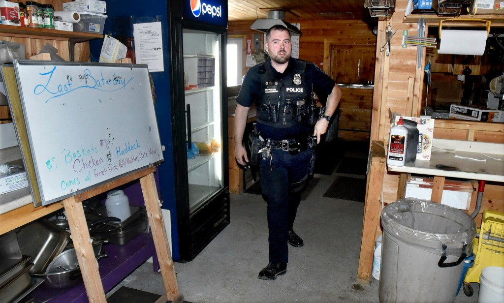 Skowhegan police officer Jake Boudreau inspects the kitchen area of the Skowhegan Lions Club food booth while he and officer Tim Williams search for evidence after a break-in and theft was discovered Sunday at the Skowhegan Fairgrounds site.