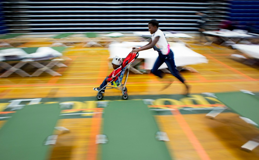 Alegria Landu, 9, pushes her brother Gabriel, 3, in a stroller at an emergency shelter for asylum seekers at the Portland Expo on Thursday.