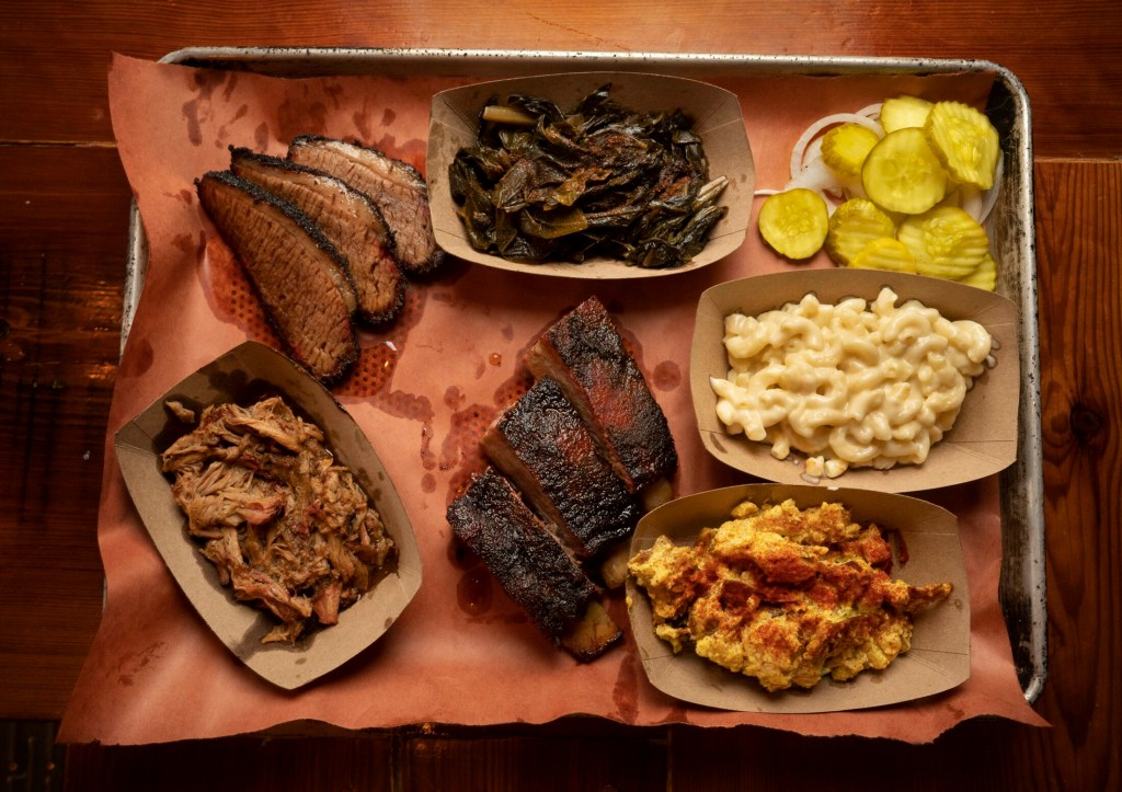 Ore Nell's shared Barbecue Platter. Clockwise from bottom left: pulled pork, brisket, collard greens, pickles and onions, mac and cheese, potato salad and St. Louis style ribs.