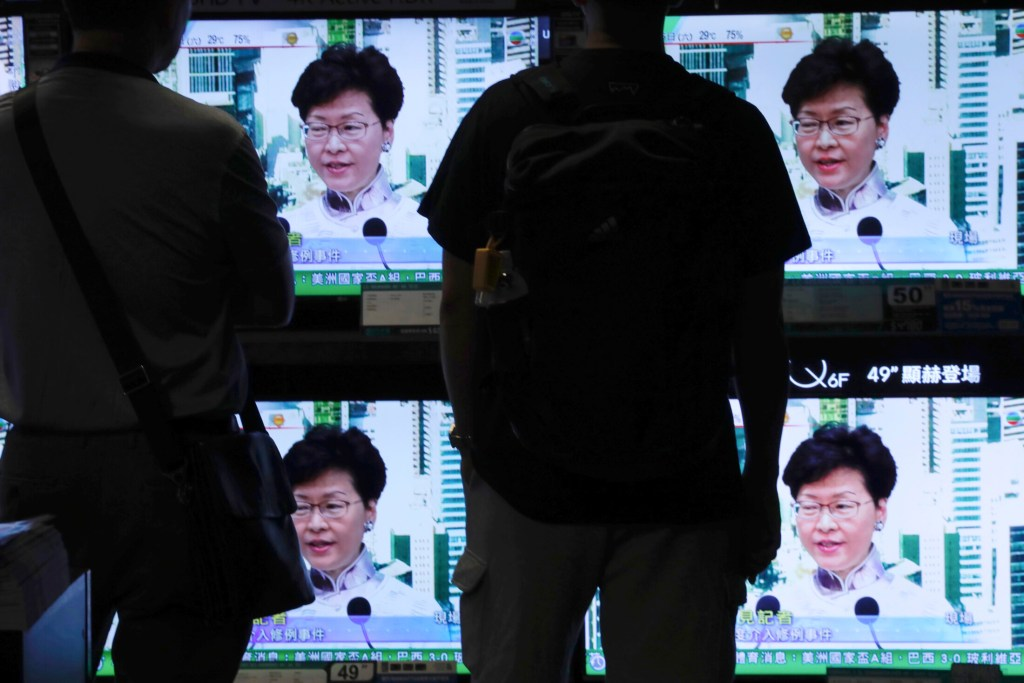 Residents watch a broadcast of Hong Kong Chief Executive Carrie Lam speaking at a press conference Saturday. Lam is suspending an extradition bill indefinitely after widespread public protests. The measure would enable authorities to send some suspects to stand trial in mainland China.