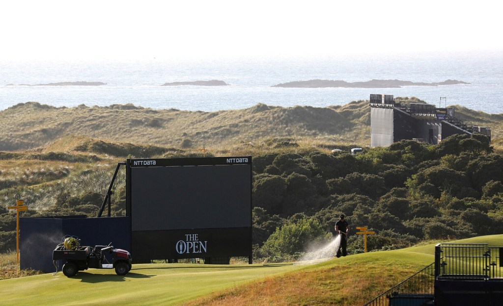 A member of the groundstaff waters the greens on the Dunluce Links course at Royal Portrush Golf Club in Northern Ireland, site of this year's British Open.