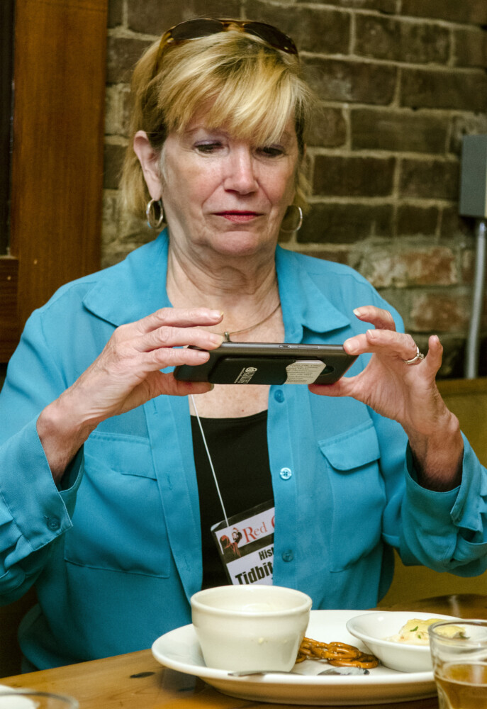 "HALLOWELL, ME - JULY 27: Before tasting it, Karen Shultz photographs her sample of beer cheese soup and ""Shrimpcargot"" during the Hallowell Historic Tidbit Tasting from Red Cloak Tours on Saturday in downtown Hallowell. According to the menu, shrimp-cargo is their version of the French delicacy, mushroom caps stuffed with garlic butter, Gulf shrimp & Brie."