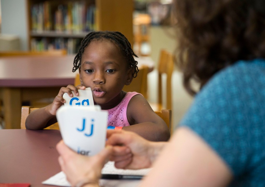 Emily Hall Greeley does an English language assessment with Stela Solani Ndombasi Mvemba, 5, at King Middle School on Wednesday. Ndombasi Mvemba is one of roughly 75 children of asylum seekers who are being processed and assessed by Portland Public Schools. Many of the children will start summer school next week.