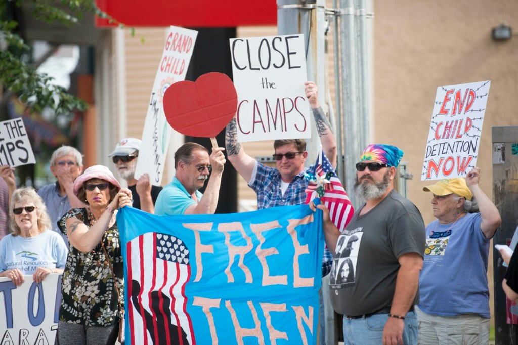 Jasmine Violette, of Albion, left, and Matthew Crane, right, hold a giant sign Friday in protest of immigration detention and family separation on the southern border on the corner of Temple and Main Streets in Waterville.
