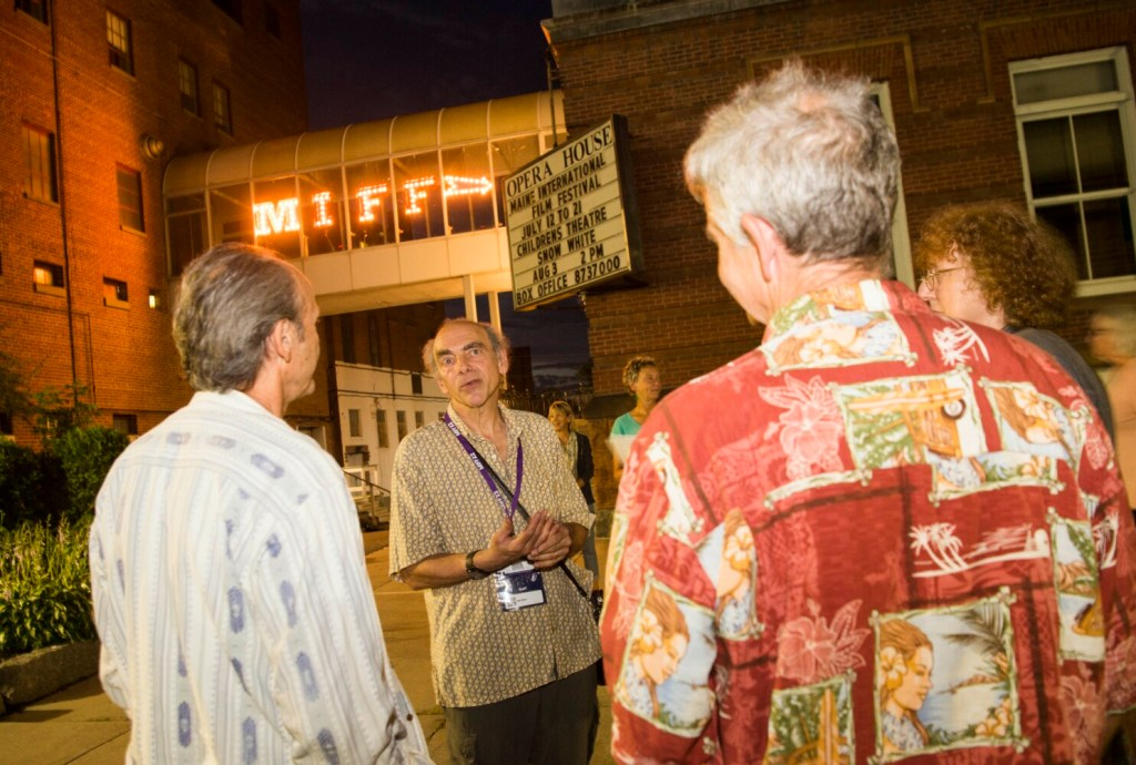 """Ken Eisen, facing forward, speaks with protesters before the Wednesday night showing of the controversial film """"Last Tango in Paris"""" during the Maine International Film Festival at the Waterville Opera House."""