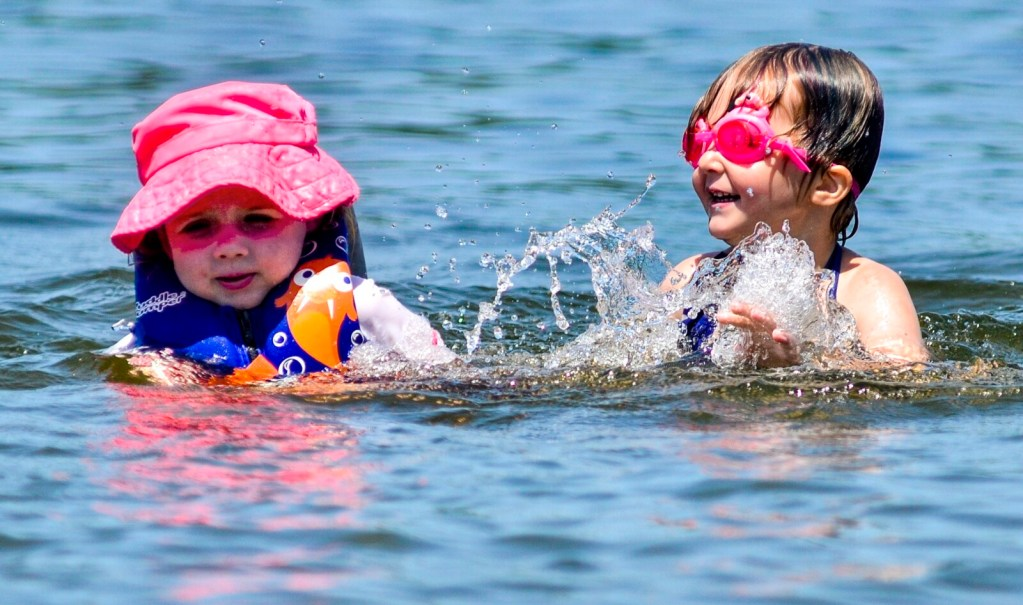 Oriana Murray, left, and Elizabeth Tripp splash on Friday in Maranacook Lake at the Winthrop town beach.
