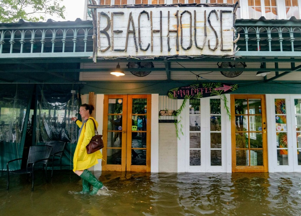 Aimee Cutter, the owner of the Beach House restaurant, walks through a storm surge from Lake Pontchartrain on Lakeshore Drive in Mandeville, La., on Saturday.