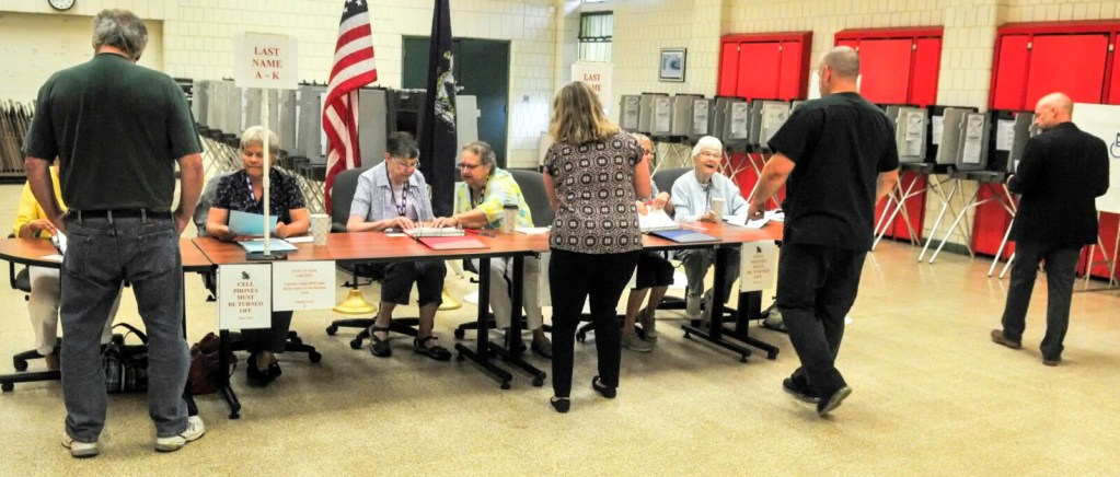 Voters pick up ballots for the school budget special election just after polls opened Tuesday at 8 a.m. at the Winthrop Town Office.