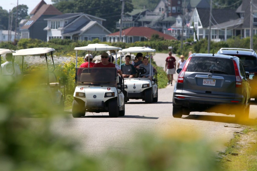 Rented golf carts squeeze through a narrow lane between passing cars and other parked golf carts on Seashore Avenue on Peaks Island on Wednesday.