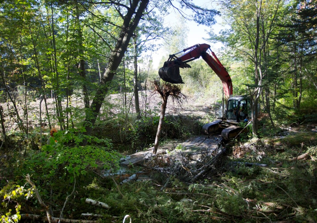 Construction crews install woody debris into the stream channel on Sept. 27 near the Maine Mall in South Portland.