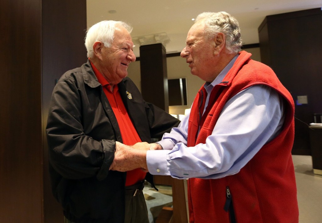 Orson Swindle, left, who was shot down during a bombing mission, shakes hands with Dick Manning, who was a forward spotter on the same mission, as they meet for the first time Saturday at the Westin Portland Harborview.