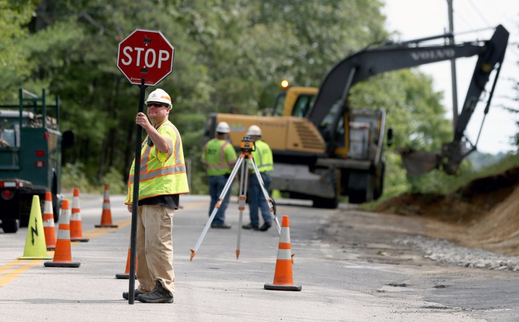 Maine Department of Transportation worker Richard Roscoe controls traffic at a job site in North Yarmouth on Sept. 6. A shortage of workers in government, both state and local, is widespread in Maine. Roscoe has worked for the transportation department for two years.