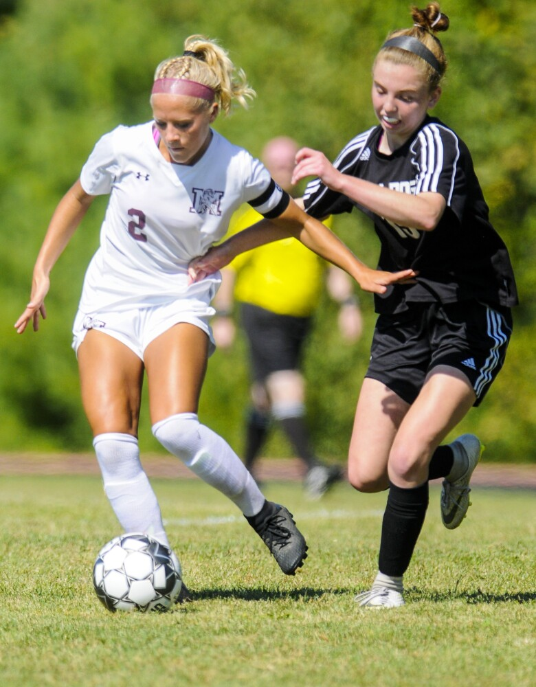 Monmouth Academy striker Audrey Fletcher, left, dribbles around Hall-Dale midfielder Rita Benoit during a game earlier this season in Farmingdale.