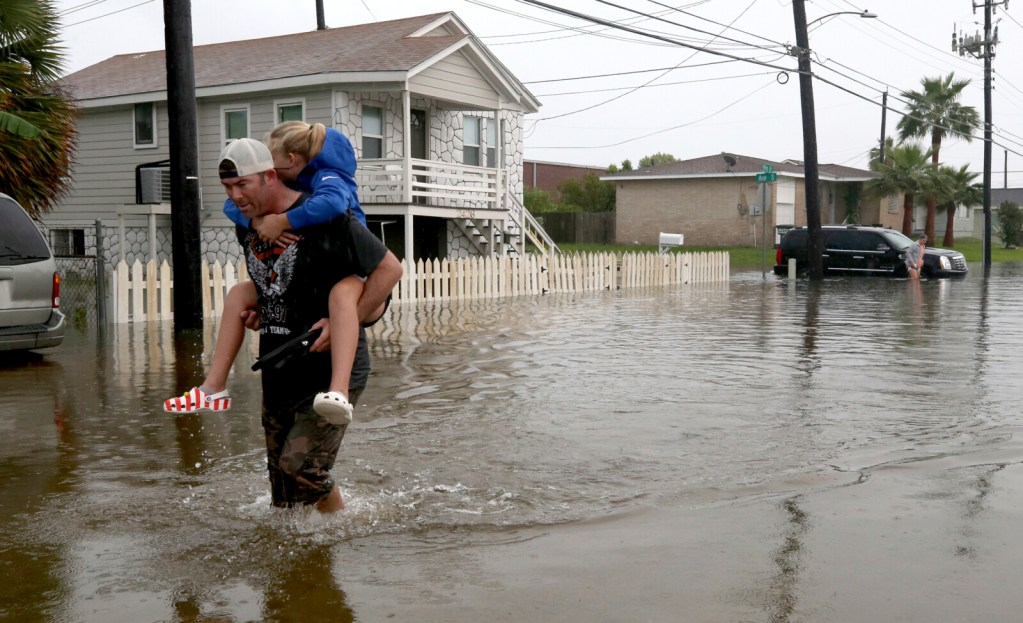 Terry Spencer carries his daughter, Trinity, through high water on 59th Street  in Galveston, Texas, on Wednesday as heavy rain from Tropical Depression Imelda caused street flooding on the island.