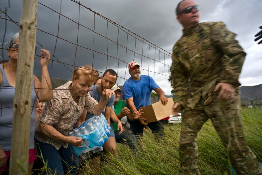 A Puerto Rican National Guard member delivers food and water brought by helicopter in the San Lorenzo neighborhood of Morovis, Puerto Rico, two weeks after Hurricane Maria hit in 2017. Money to rebuild a National Guard base in Puerto Rico is being redirected to build Trump's border wall.