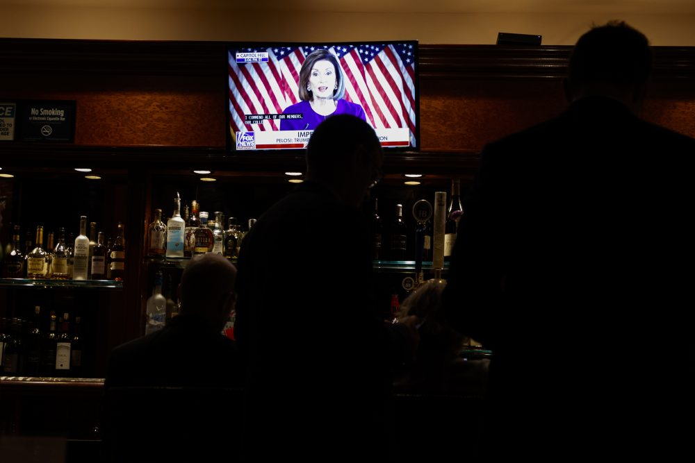 Journalists watch Speaker Nancy Pelosi announce a formal impeachment inquiry of President Trump, in the Trump Tower bar.