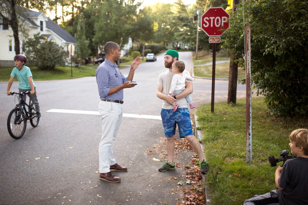 """Portland mayoral candidate Spencer Thibodeau chats with John Osterman while canvassing in the Rosemont neighborhood last month. Thibodeau, who grew up in the neighborhood, says he would be an """"honest broker"""" as mayor."""
