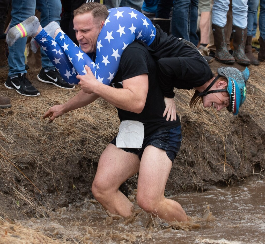 Jesse Mead carries his wife Amy through the water obstacle Saturday  at Sunday River in Newry. The Portland couple finished in fourth place.