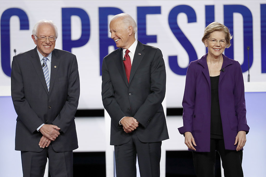 Leading Democratic presidential candidates Bernie Sanders, Joe Biden and Elizabeth Warren stand on stage before Thursday's Democratic presidential primary debate at Otterbein University in Westerville, Ohio.