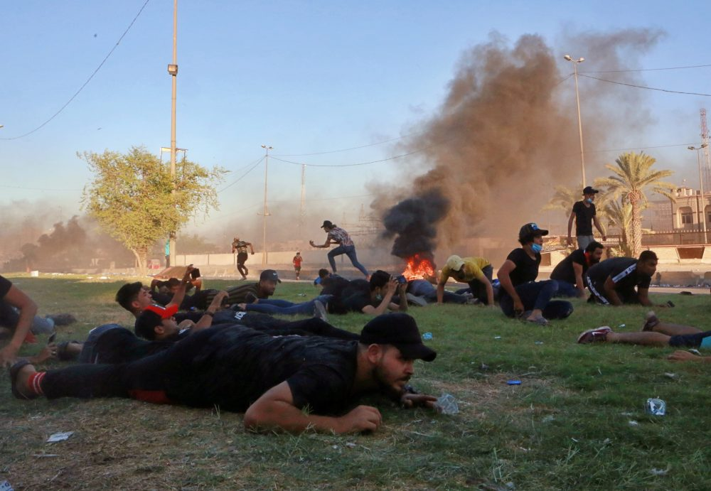 Anti-government protesters take cover while Iraq security forces fire during a demonstration in Baghdad, Iraq on Friday. Thousands have taken to the streets of several areas in oil-rich Iraq to protest against corruption, lack of jobs and poor services.