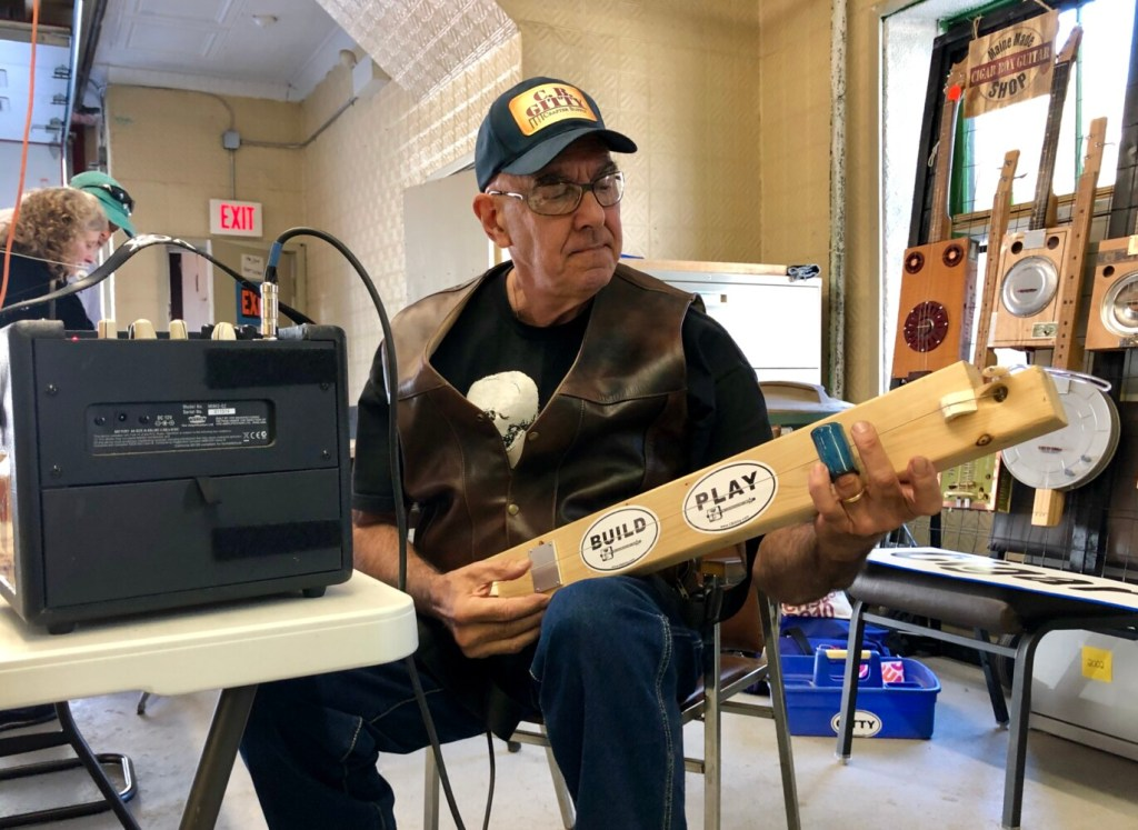 Marty Tauber of Maine Made CBGs plays a diddley bow Sunday at Hallowell's third annual Maine Luthiers Showcase. He made the instrument out of a board.