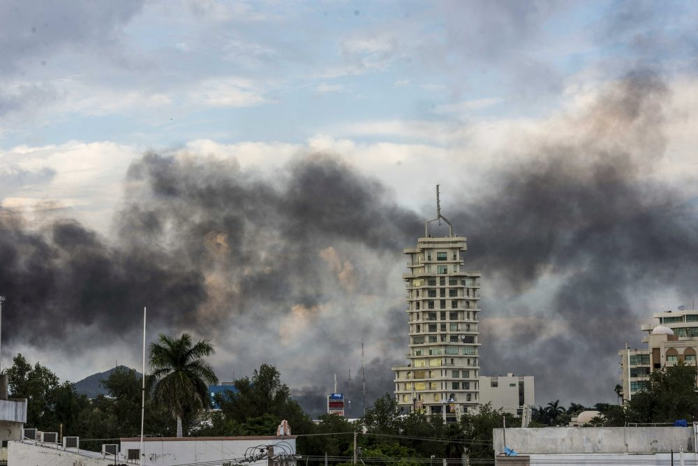 """Smoke from burning cars rises in Culiacan, Mexico, on Thursday. An intense gunfight with heavy weapons and burning vehicles blocking roads raged in the capital of Mexico's Sinaloa state after security forces located one of Joaquín """"El Chapo"""" Guzmán's sons, who is wanted in the U.S. on drug trafficking charges."""