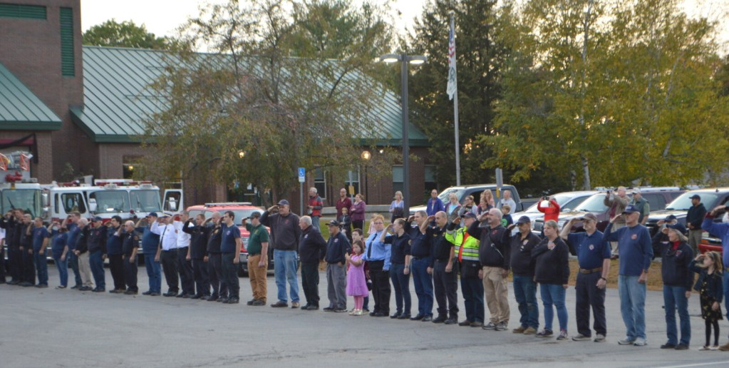 Firefighters salute while others put their hands over their hearts Tuesday evening as they welcome Farmington Fire Rescue Chief Terry Bell home from a Portland hospital more than three weeks after he was critically injured in a deadly propane explosion.