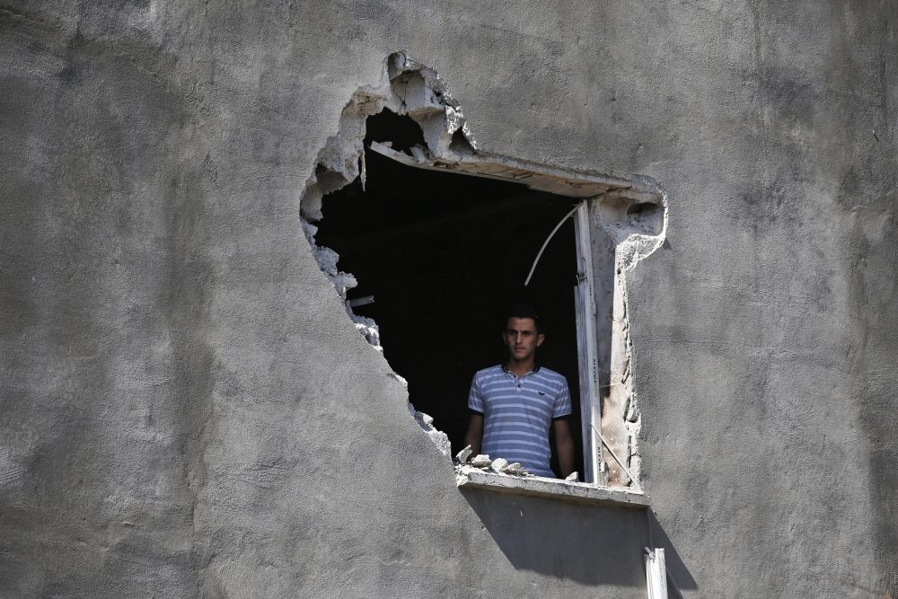 "A resident looks out from a hole in a house that was damaged by a mortar fire in the Turkish town of Akcakale on Saturday. President Trump has withdrawn U.S. forces in Syria, saying he wanted to stop getting involved with ""endless wars."""