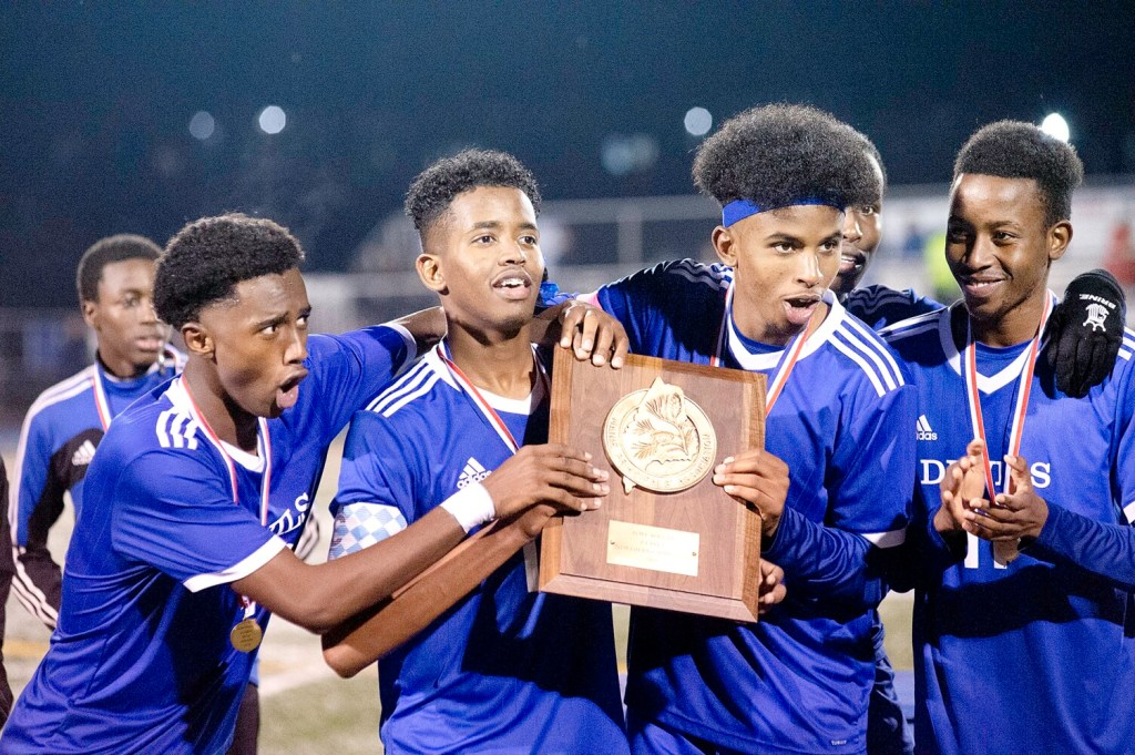 Lewiston High School seniors Suab Nur, left, Moubarek Abdourahman, Bilal Hersi and Abdilahi Abdi celebrate with the Maine Principal's Association trophy after beating Brunswick 3-1 to win the North Regional Championship in bath on Tuesday.