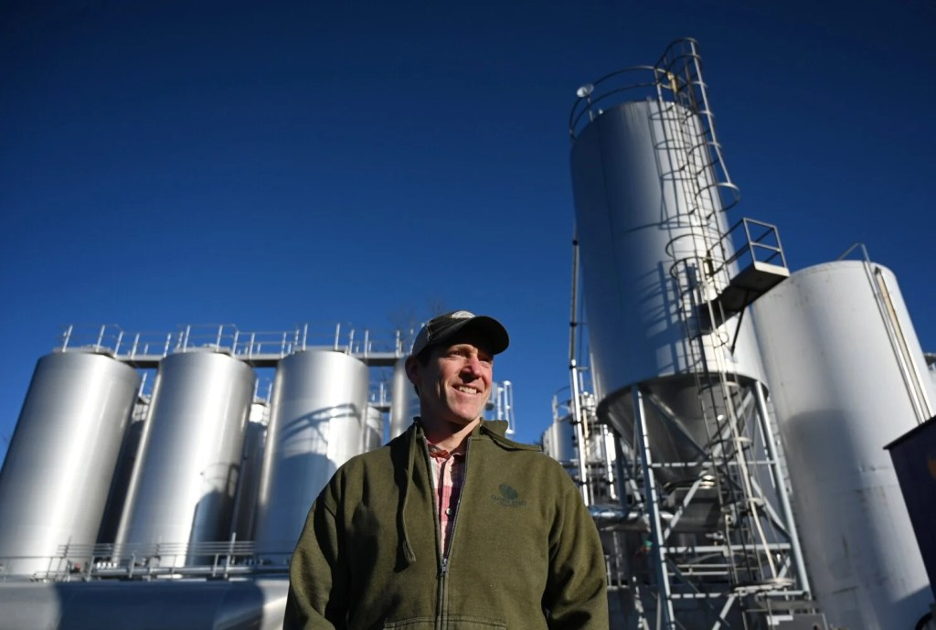 Master Brewer Jason Perkins outside in front of the fermentation tanks, left and the spent grain and spent yeast tanks are to the right, at Allagash Brewing Co. in Portland. the company uses about half the amount of water to produce its beer as the national average, evidence of its commitment to sustainability practices.