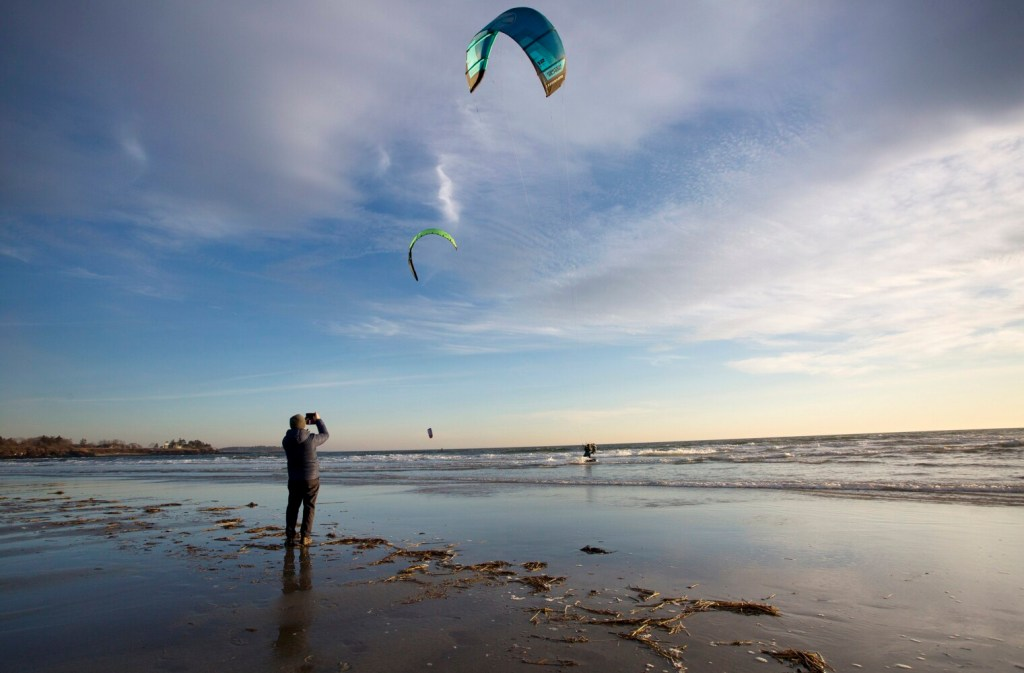 A beachgoer takes pictures of kitesurfers at Higgins Beach in December.
