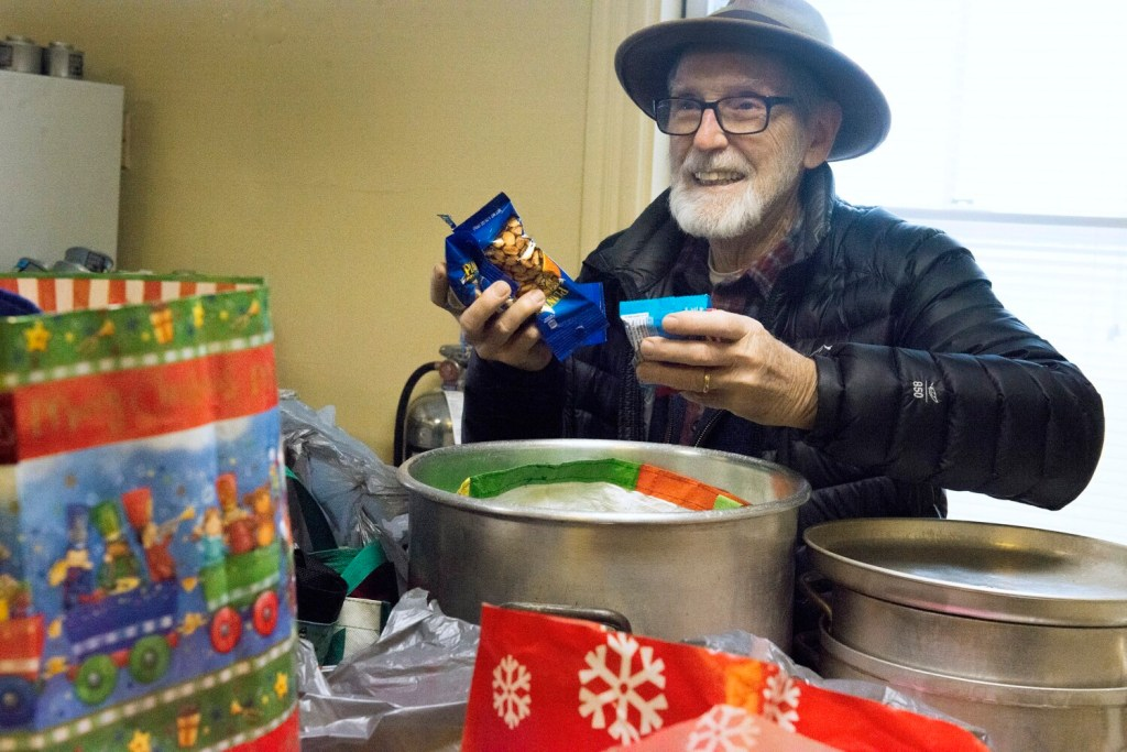 Peter Carleton, a volunteer at the church, looks through the contents of some of the gift bags donated to the warming center at St. Luke's Cathedral in Portland on Wednesday.