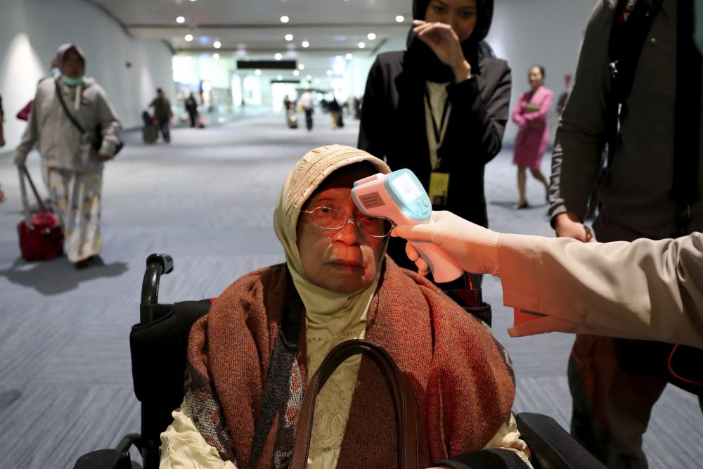 A health official scans the body temperature of a passenger as she arrives Wednesday at the Soekarno-Hatta International Airport in Tangerang, Indonesia.