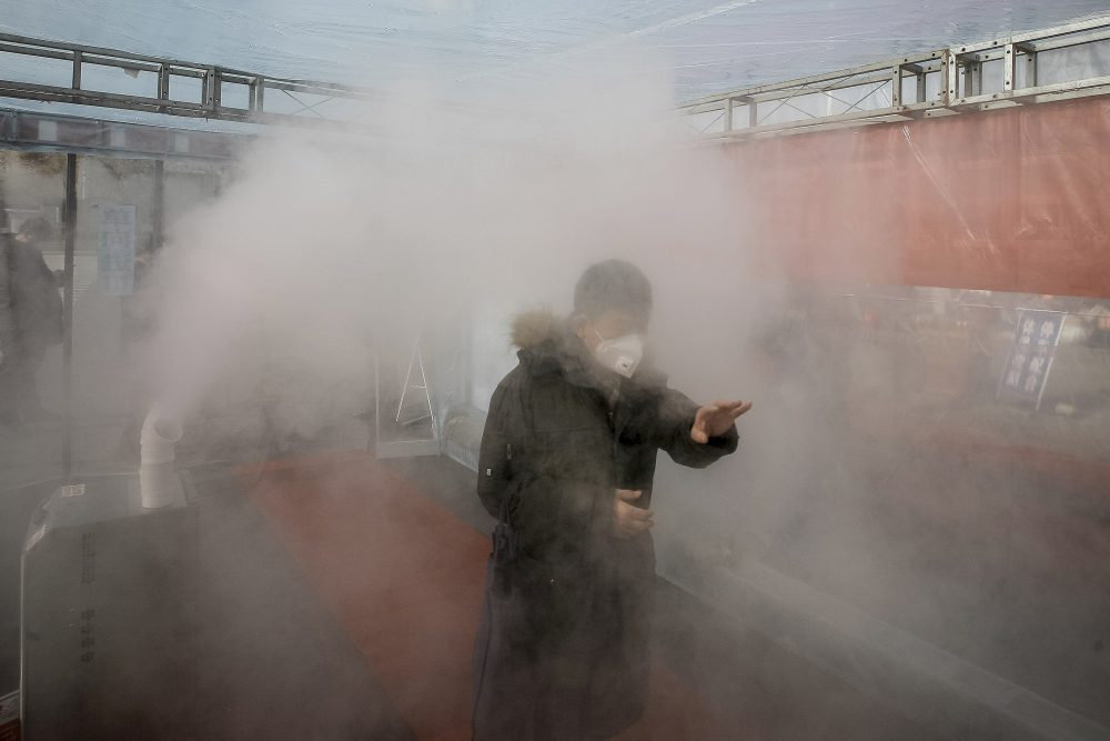 A man walks through a cloud of disinfectant spray to return home in China's Tianjin Municipality on Tuesday. There are no proven treatments or vaccines for the new coronavirus, officially named COVID-19.