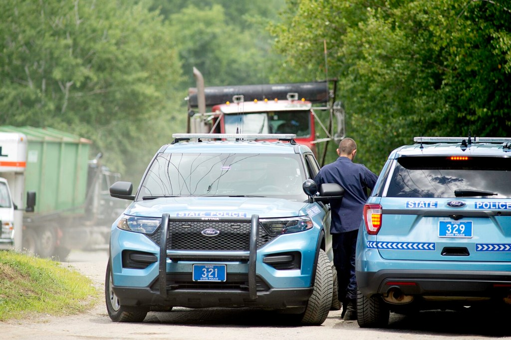 """Maine State Police officers block access to the rear of the Narrow Gauge Distributors """"Keeping the Supply High"""" building at 374 High St. in Farmington last Tuesday while marijuana plants are loaded into a shipping container, at left."""
