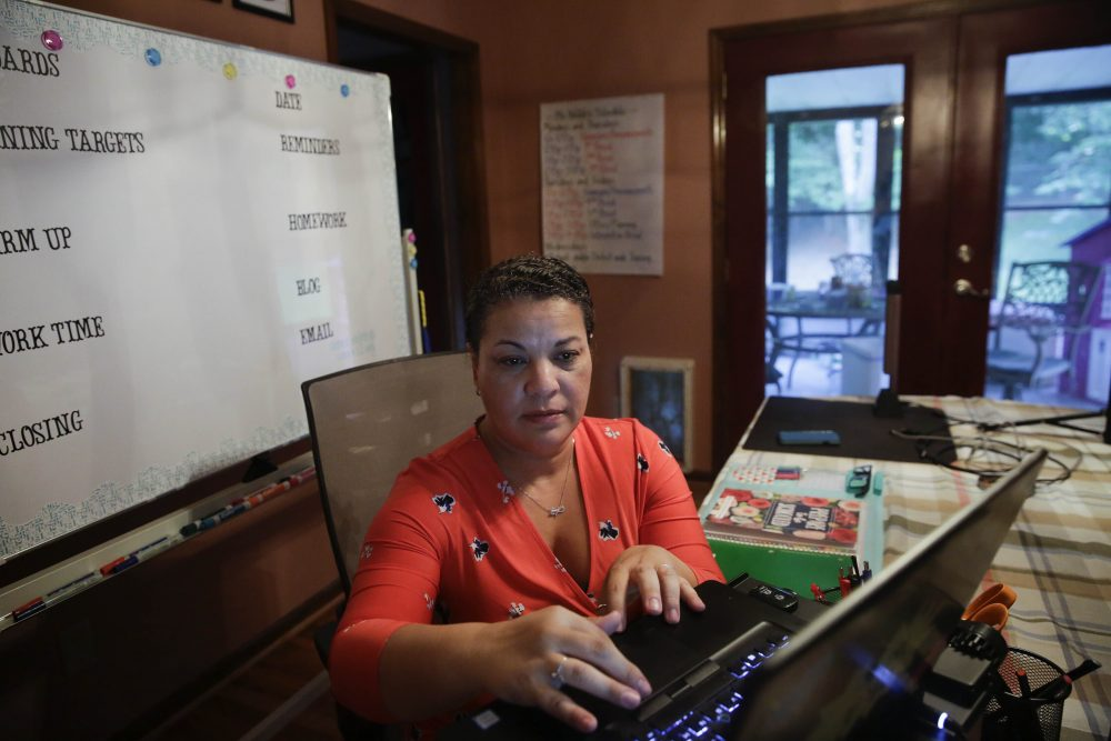 Aimee Rodriguez Webb works on her computer reading emails at her dinning room table that she set up as a virtual classroom.