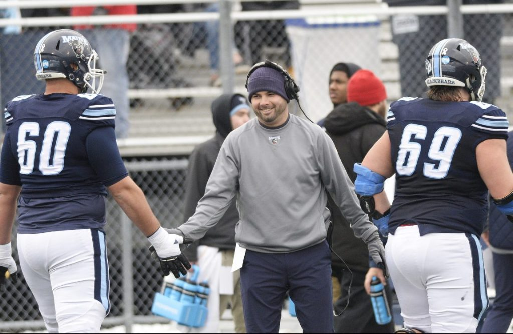 """University of Maine coach Joe Harasymiak congratulates players in the game against Jacksonville State on Dec. 1. """"I've always loved the environment of the competition, the stress, everything that goes with it,"""" he said."""