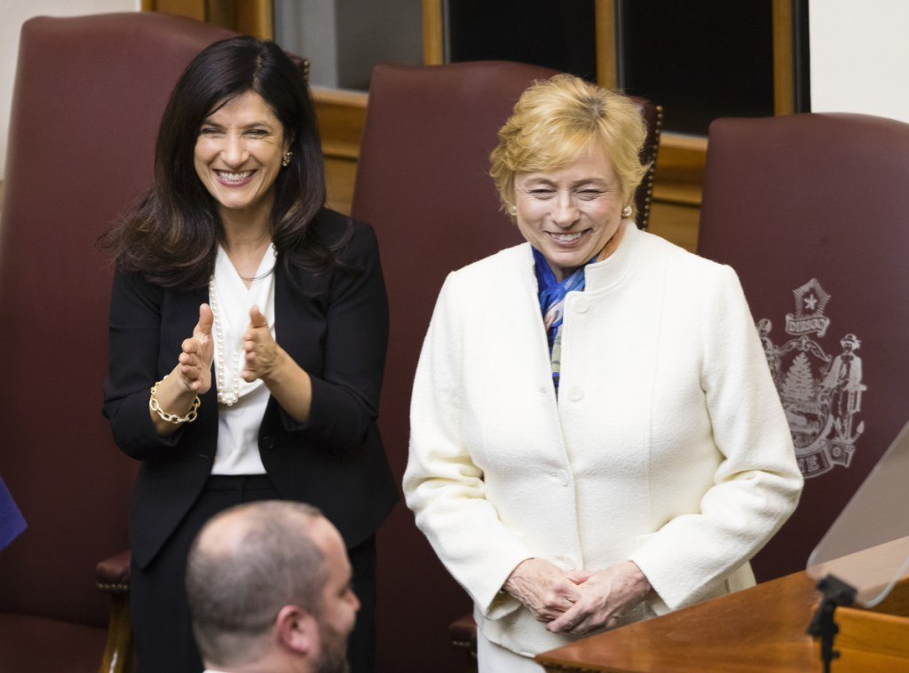 Gov. Janet Mills receives applause from supporters including House Speaker Sara Gideon, left, after her budget address to the Legislature on Monday evening.