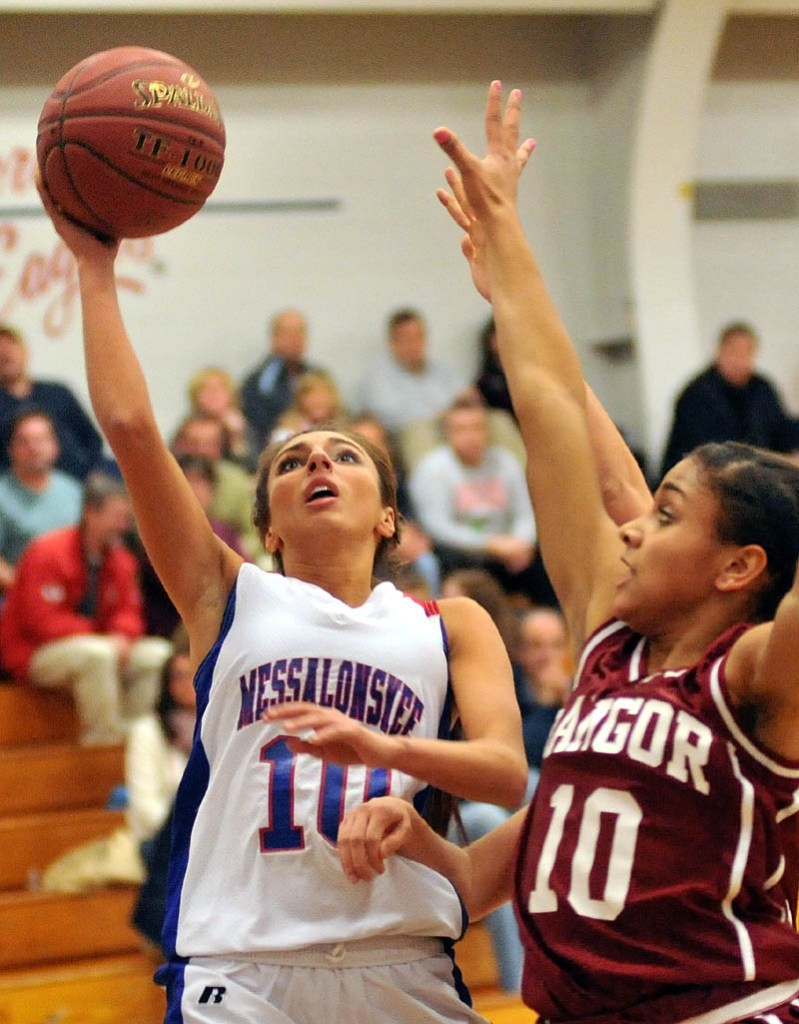 TO THE HOOP: Messalonskee High School's Mary Badeen, left, drives for a layup while Bangor High School's Denae Johnson plays defense in the first half of their game Tuesday in Oakland.