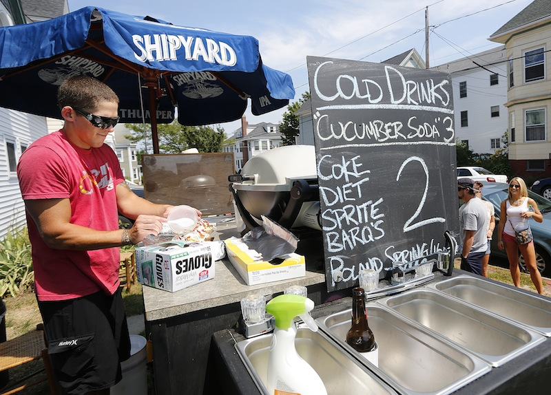 """Eliot Poirier makes some Gyros for customers from his food cart on the corner of Vesper Street and Moody Street on Munjoy Hill in Portland near the """"Gentleman of the Road Stopover"""" concert on Saturday, Aug. 4, 2012."""