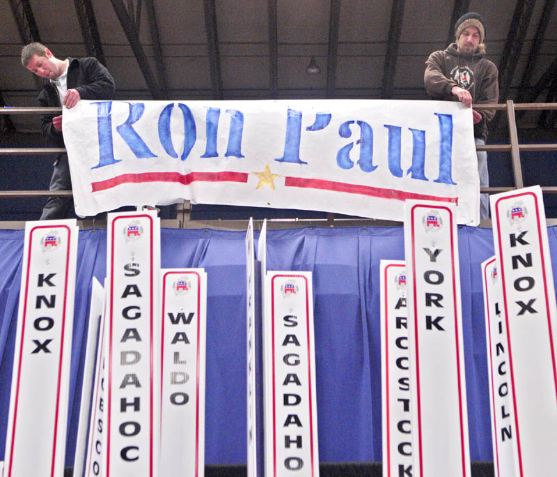 Toby Hoxie, of Hallowell, left, and Chad Libby, of Winthrop, hang up a sign for Ron Paul in May at the state Republican convention in Augusta.