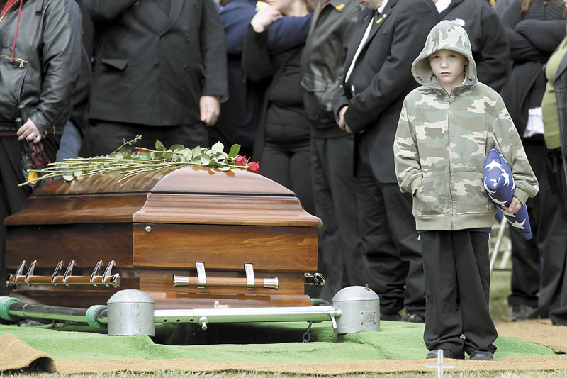 """Nicholas Weichel, son of Rhode Island National Guard Sgt. Dennis Weichel Jr., who was killed in Afghanistan, stands next to his father's casket during funeral services April 2 at the state Veterans Cemetery in Exeter, R.I.. Weichel Jr., was struck and killed by an armored vehicle March 22 in Afghanistan while saving an Afghan boy. It was once President Barack Obama's """"war of necessity."""" Now, it's America's forgotten war. The Afghan conflict generates barely a whisper on the U.S. presidential campaign trail. It's not a hot topic at the office water cooler or in the halls of Congress — even though 88,000 American troops are still fighting here and dying at a rate of one a day."""