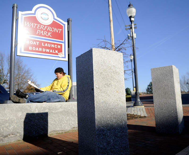 """Thomas Blancato reads Tuesday at the entrance of the waterfront park in Gardiner, as temperatures hovered in the mid-50s F. Blancato said he reads outside every day he's not working. """"It's a nice spot right here,"""" he said."""