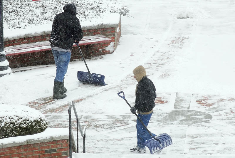 Workers shovel snow on Wednesday in front of Key Plaza in downtown Augusta.