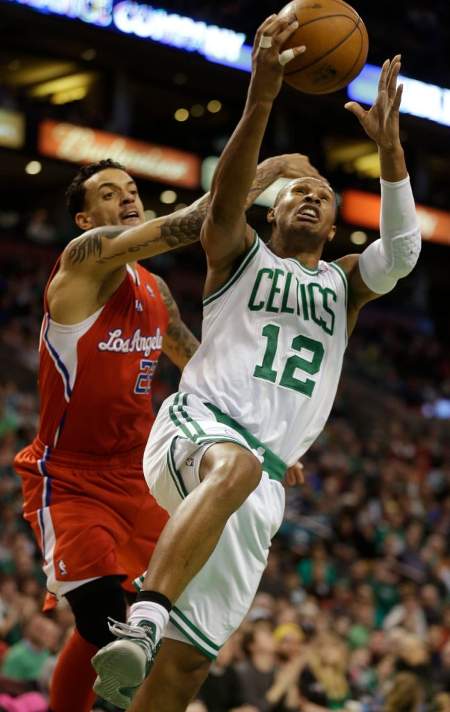 Boston guard Leandro Barbosa goes up for a layup while harassed by Los Angeles forward Matt Barnes during Sunday's game in Boston, won by the Celtics.