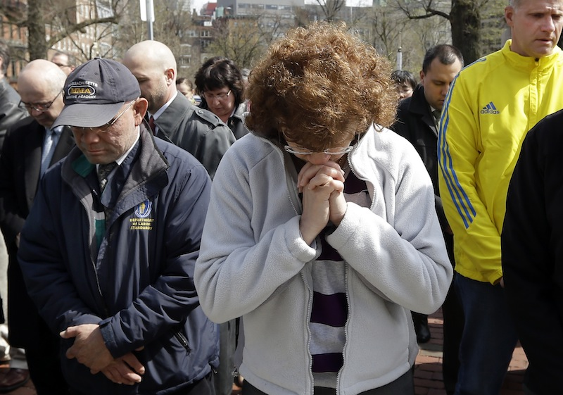 People pause for a moment of silence near the Statehouse in Boston at 2:50pm, Monday, April 22, 2013, exactly one week after the first bomb went off at the finish area of the Boston Marathon. (AP Photo/Elise Amendola)
