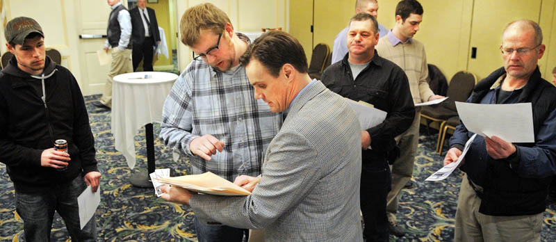 Recruiter David Bartholomew, center, reviews a resume from Knowell Matthews of Fairfield on Wednesday during a job fair for Summit Natural Gas in Augusta. More than 100 people attended the event to learn how to apply for positions with the Colorado firm that plans to install and manage a natural gas pipeline in Kennebec County.