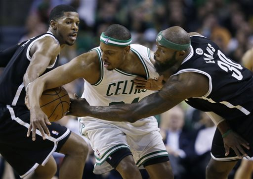 Brooklyn Nets forward Reggie Evans (30) reaches for the ball as Boston Celtics forward Paul Pierce, center, tries to control it while Nets guard Joe Johnson watches during the second half of an NBA basketball game in Boston, Wednesday, April 10, 2013. The Nets won 101-93. (AP Photo/Elise Amendola) TD Garden